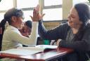 Imagem ilustrativa mostrando uma professoram brincando com sua aluna em sala de aula