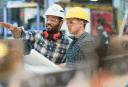 Imagem ilustrativa mostrando dois profissionais com vestimentas para trabalho em obra